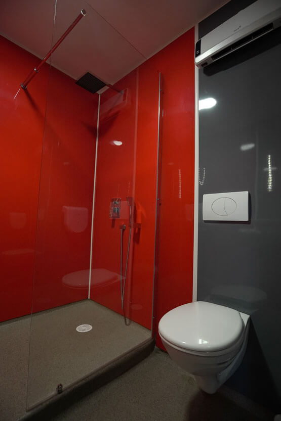 Vue sur la douche d'une chambre d'hôtel rénovées avec des plaques PVC rouges et grises